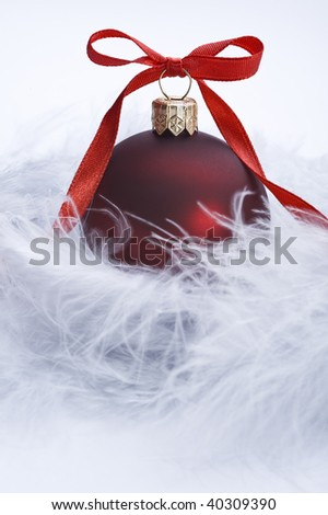 christmas ball with decorative red ribbon on feather