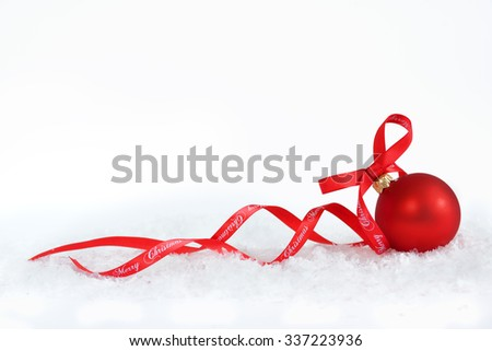 Christmas ball with red ribbon on artificial snow flakes. - stock photo