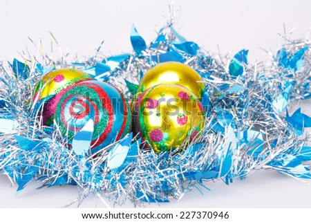 Christmas balls and blue garland on gray background. - stock photo