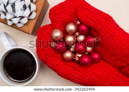 Christmas balls in hands, coffee and gift on wooden background - stock photo