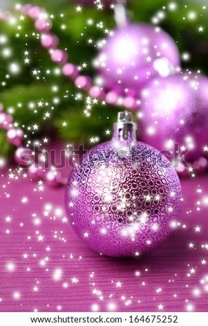 Christmas balls on fir tree, on color background - stock photo
