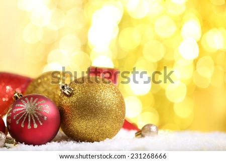 Christmas balls on snow on bright background