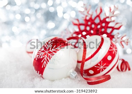 Christmas balls with painted snowflakes and ribbon against holiday lights.