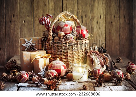 Christmas Basket with Vintage Gifts and Shining Candle. Red balls, Pine cones, Snowflakes, Boxes on Wooden Table. Warm Toned effect - stock photo