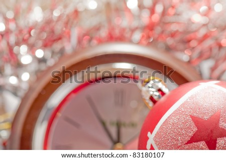 Christmas bauble and five to twelve on the blurred clock - stock photo