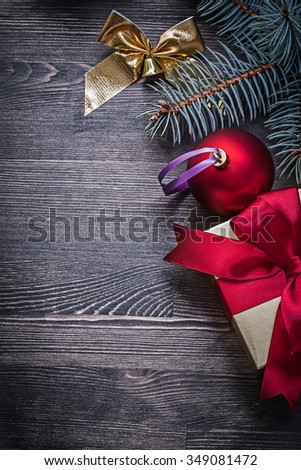 Christmas bauble bow pine twig present box on wood board. - stock photo
