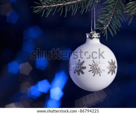 Christmas bauble hanging on fir branch in dark blurry back - stock photo