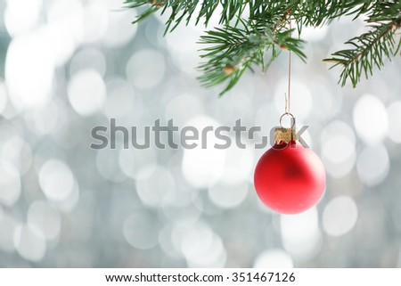 Christmas bauble on a fir branch and glitter background - stock photo