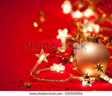 Christmas bauble with star-shaped lights and tinsel on red background - stock photo