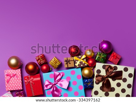 Christmas baubles and gifts on violet background - stock photo