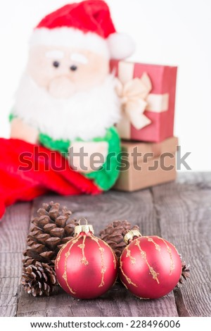 Christmas baubles and pine cones with Santa Claus toy background