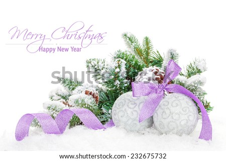 Christmas baubles and purple ribbon with snow fir tree. Isolated on white background with copy space - stock photo
