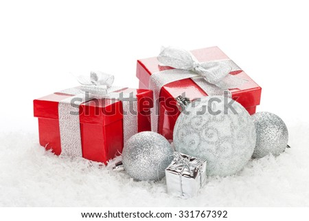 Christmas baubles and red gift boxes over snow with copy space - stock photo