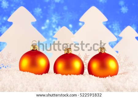 Christmas baubles and trees on blue background