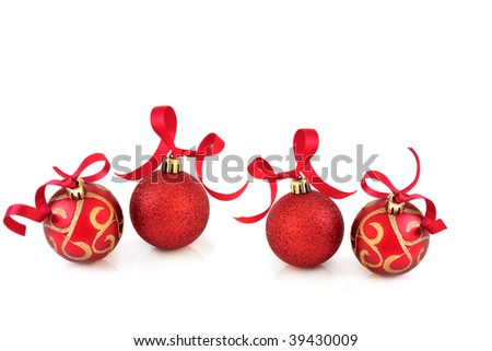 Christmas baubles in sparkling red and gold with ribbons, over white background with reflection.