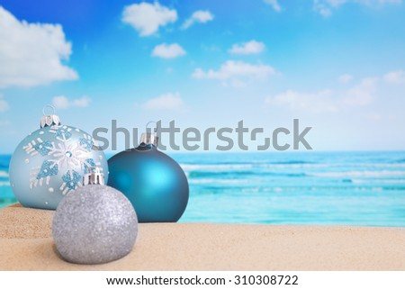 Christmas baubles in the sand on a beach on a bright and sunny day. - stock photo