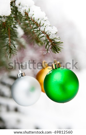 Christmas baubles on a snowy pine on a cold winter day - stock photo
