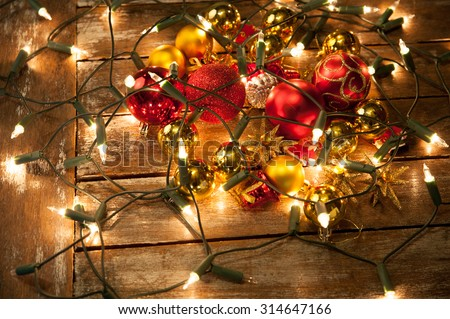 christmas baubles scattered on a wooden table wrapped in fairy lights