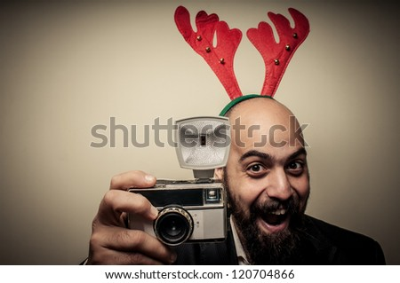 christmas bearded man holding old camera on grey background - stock photo