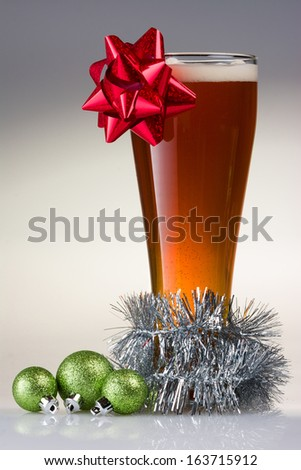Christmas Beer with a Bow, garland, and Ornaments - stock photo