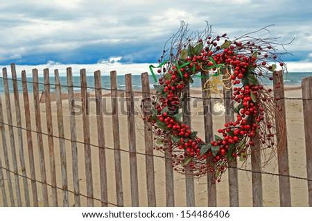 christmas berry wreath with starfish and seashells on beach fence - stock photo
