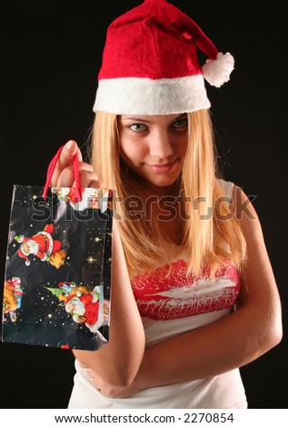 Christmas blonde girl offer a gift in a bag, black background