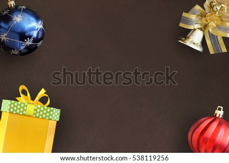 Christmas blue and red wavy ball, decorative bell, gift box on dark background. Flat lay with copy space.
