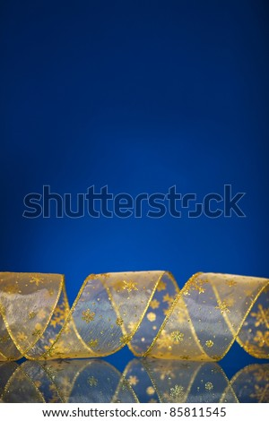 Christmas border from gold ribbon on dark blue background with reflection. Shallow DOF - stock photo