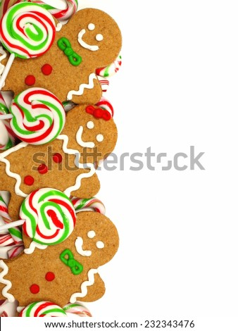 Christmas border of colorful gingerbread men and candies over a white background - stock photo
