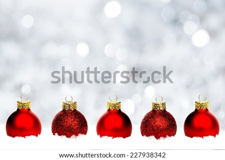 Christmas border of shiny red baubles resting in snow with twinkling silver background - stock photo