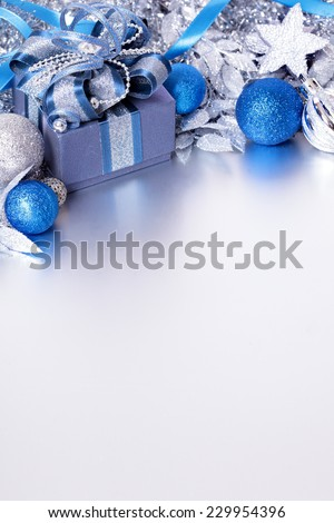 Christmas border with decorations laid on a matte silver surface. Space for copy. - stock photo