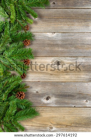Christmas border with pine tree branches, and cones on rustic wooden boards. Layout in vertical format.   - stock photo