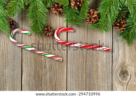 Christmas border with pine tree branches, cones and candy canes on rustic wooden boards.  - stock photo