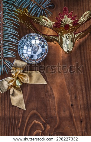 christmas bow bauble mask branch of fir tree on vintage wood board. - stock photo