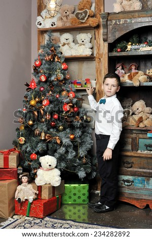 Christmas boy around Christmas tree with gifts