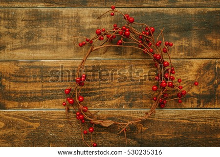 Christmas branch with red berries on a rustic wooden background