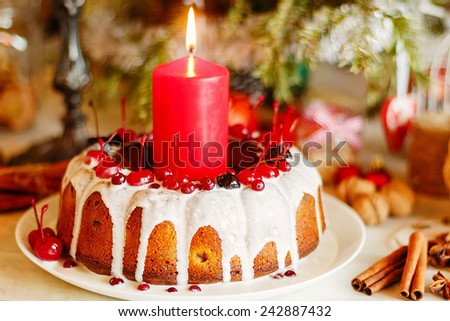 Christmas bundt cake with white glaze decorated with cranberries and cherries. Shallow focus