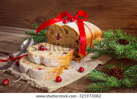 Christmas cake with cranberry on an old wooden background, tinted