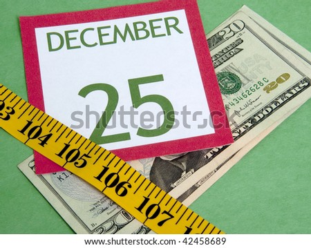 Christmas calendar page squeezed by a measuring tape representing a tight holiday budget. - stock photo
