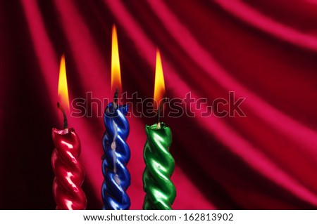 Christmas candle  against purple drapery - stock photo