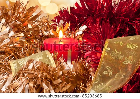 Christmas Candle burning surrounded by golden, red and green ribbon - stock photo