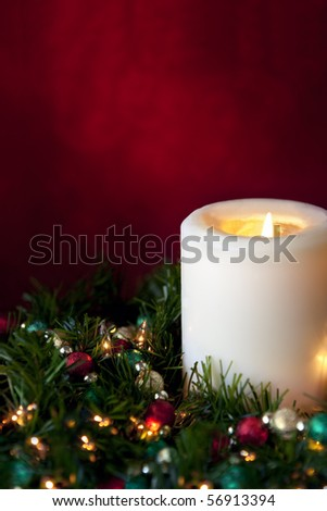 Christmas candle, nestled in a garland with fairy lights and baubles.  Rich red tapestry background. - stock photo