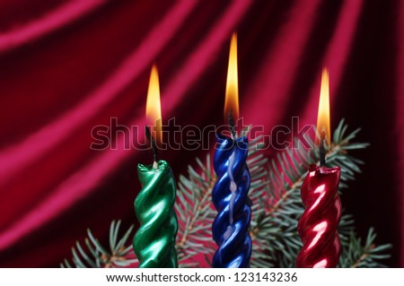 Christmas candle  with decoration on a purple drapery - stock photo