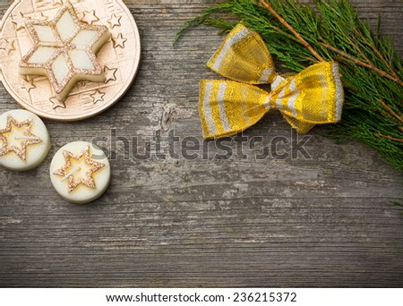 Christmas candles and fir-tree branch on rustic wooden table - stock photo