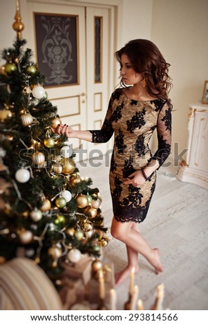 Christmas Candles. Happy Surprised Woman Posing Near Christmas Tree at home.   - stock photo
