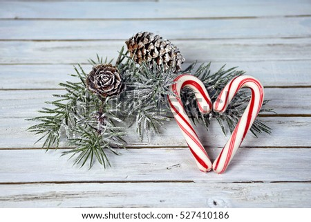Christmas candy cane heart with frosted pine on gray rustic wood