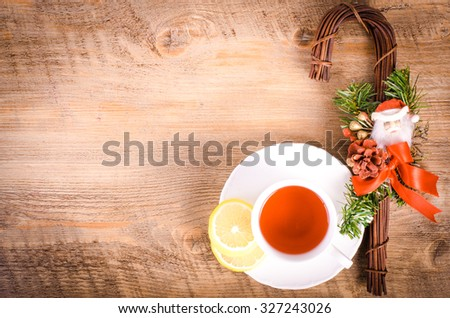 Christmas cane and cup of tea on wooden background. Christmas and New Year decoration. Free space for text. - stock photo