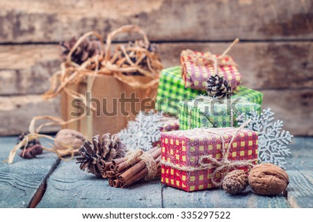 Christmas card - beautifully wrapped gifts and decor from cones, nuts and cinnamon on rustic wooden table