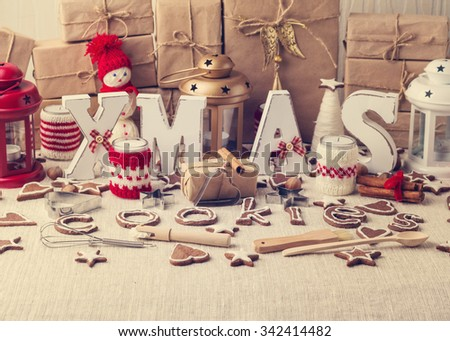 Christmas card. Christmas decorations - letters XMAS, gifts, cookies, candles, nuts, spices. Selective focus.