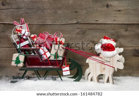 Christmas card decoration: elks pulling santa sleigh with presents on a wooden background - funny greeting card in Country Style  - stock photo